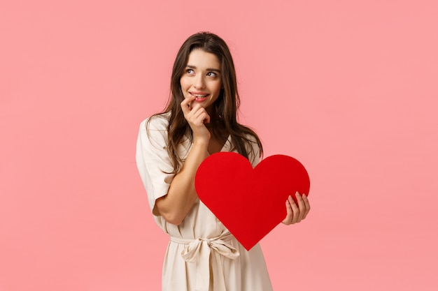 Coquettish and silly, dreamy cute, alluring brunette woman in dress, look left imaging perfect date, touching lip and smiling with tempting, eager expression, holding valentines heart, love concept