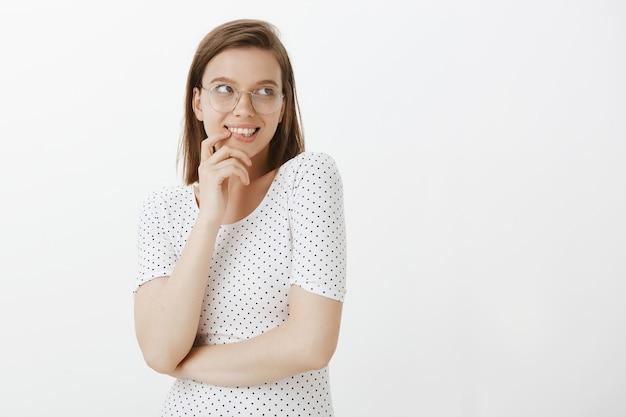 Кокетливая глупая женщина в очках улыбается, краснеет и смотрит прямо на ваш логотип