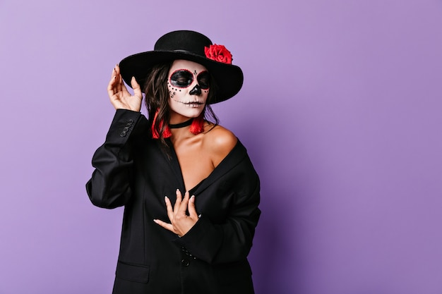 コケティッシュな女性は目を下げ、ハロウィーンの肖像画のためにマフィアの服を着てポーズをとった。