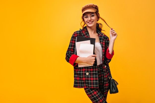 Coquettish woman in plaid outfit poses with notebooks