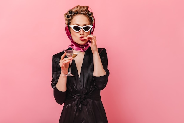 Coquettish woman in silk dress and glasses licks her finger and holds martini