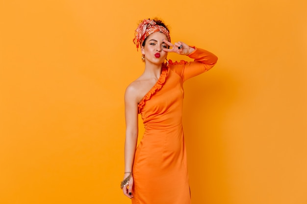 Coquettish woman in silk long dress and headband blows kiss and shows peace sign on orange space.