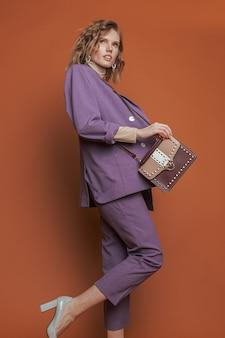 コケティッシュな若い女性がベージュルビーのバッグと紫のスーツでポーズします。