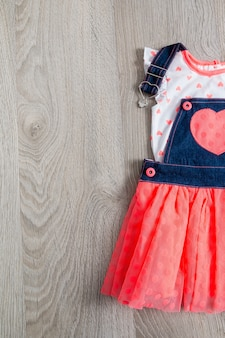 Кораллово-синее платье, комбинезон с сердцем на сером деревянном фоне. наряд маленькой девочки. вид сверху. скопируйте пространство.
