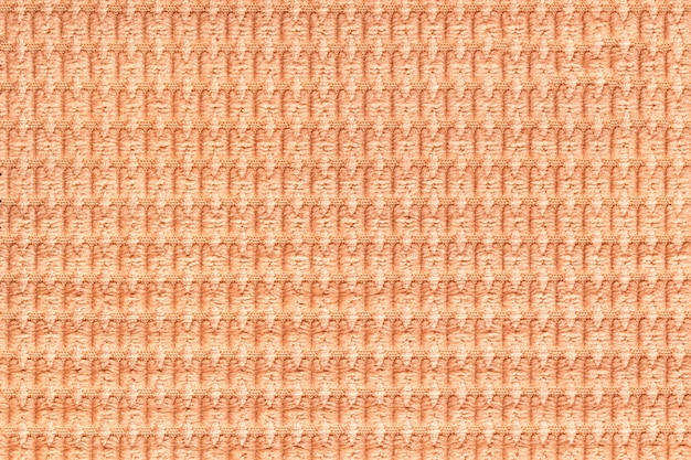 Coral background from soft fleecy fabric close up, texture of textiles macro,