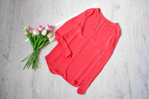 Коралловая кофточка, букет тюльпанов. модная концепция, деревянный фон