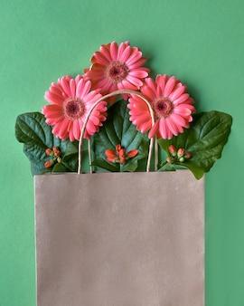 緑の紙の壁、コピー領域にサンゴガーベラデイジーの花とクラフトパパーショッピングバッグ