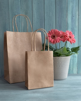 Coral gerbera daisy flowers and craft papper shopping bags on rustic background,
