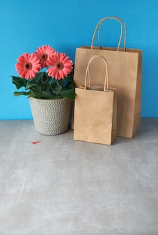 Coral gerbera daisy flowers and craft papper shopping bags. springtime sale concept image, copy-space
