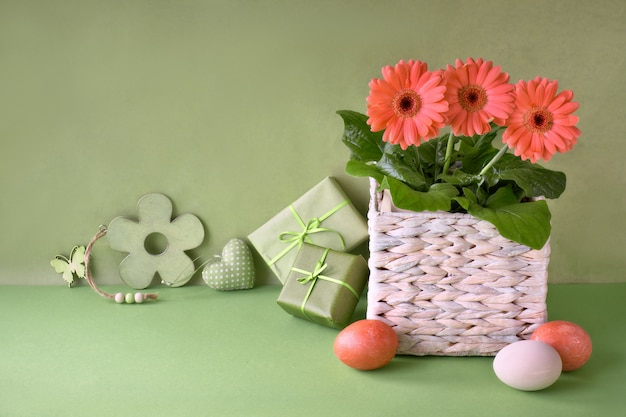 Coral gerbera daisy flowers, easter eggs and spring decorations on green paper, copy-space