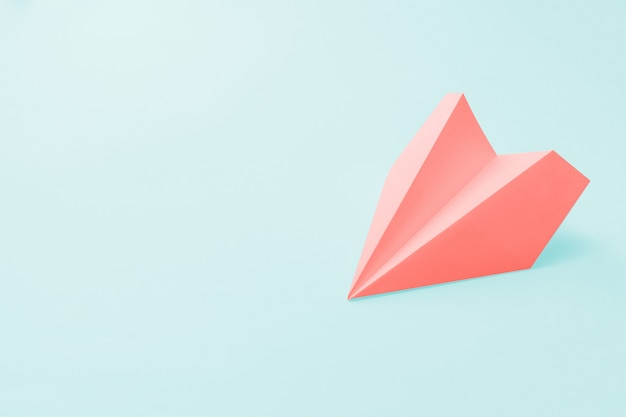 Coral paper plane on a pale blue