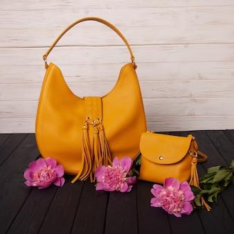 黒い木のテーブルの上の珊瑚の牡丹と黄色い革のバッグ。