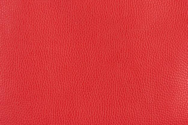 コーラルレッドの質感の滑らかな革の表面の背景、小さな木目