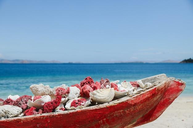 Labuan bajo의 바다 경치와 함께 해변의 긴 나무 용기에 수집된 산호초