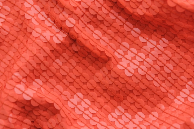 Coral shiny fabric with sequins, abstract background.