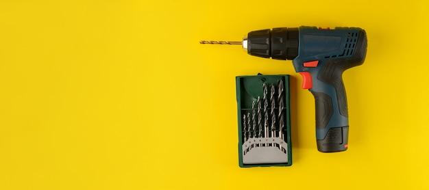 Аккумуляторная дрель со сверлами, изолированные на желтом