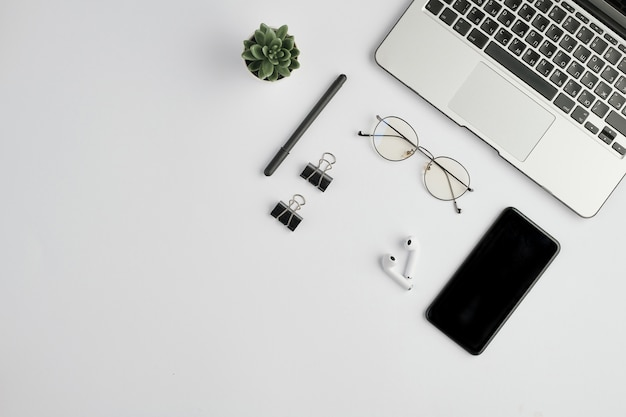Cordless earphones, eyeglasses, pen, clips, mobile gadget, small green domestic plant and laptop on white space