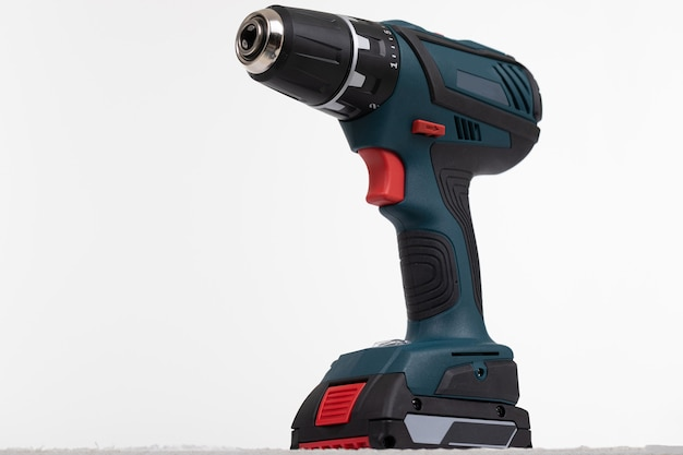 Cordless electric drill close-up on a white wall