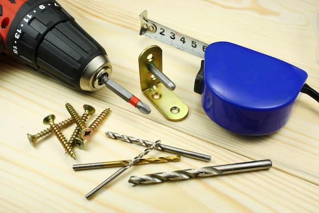 Аккумуляторная отвертка со строительными инструментами на деревянном столе
