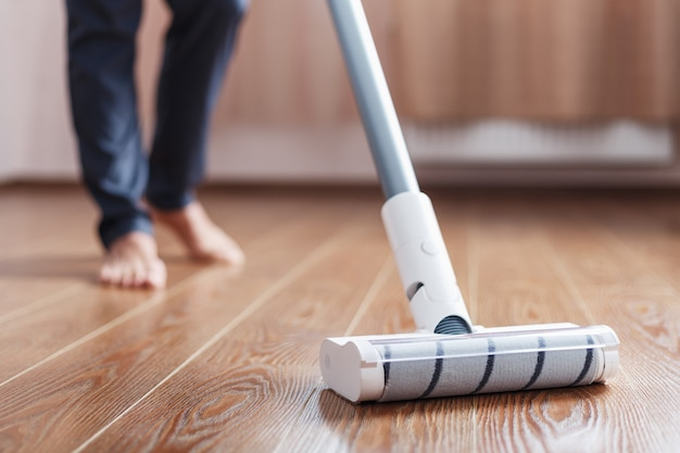 A cordless vacuum cleaner cleans the parquet in the living room with the lower part of the legs