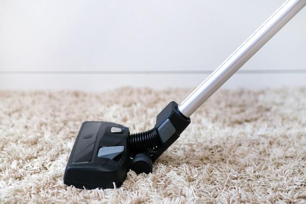 Аккумуляторный пылесос используется для чистки ковра в комнате. работа по дому с новым ручным пылесосом. уборка дома, уход и концепция технологии.