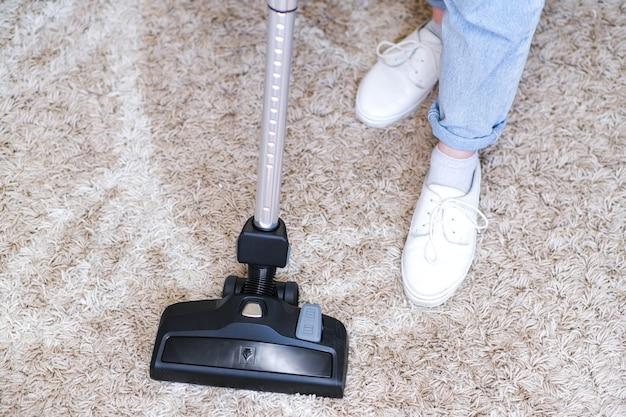 무선 진공 청소기는 방의 카펫을 청소하는 데 사용됩니다. 새로운 휴대용 진공 청소기로 집안일. 집 청소, 관리 및 기술 개념입니다.