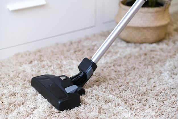 コードレス掃除機は、部屋のカーペットを掃除するために使用されます。新しいハンドヘルド掃除機での家事。ハウスクリーニング、ケア、テクノロジーのコンセプト。