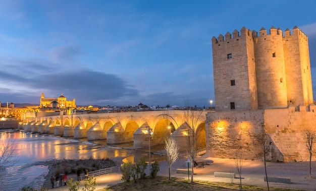 Кордова, испания, старый город, замеченный с реки на закате.