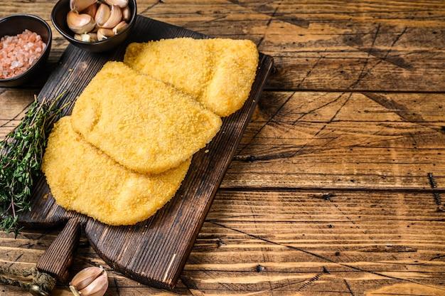 Котлеты из мяса cordon bleu с панировочными сухарями на деревянной доске на деревянном столе. вид сверху.