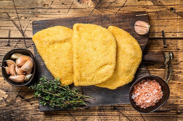 木製のテーブルの上の木の板にパン粉とコルドンブルーの肉カツレツ。上面図。