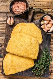 木の板にパン粉を添えたコルドンブルーの肉カツレツ