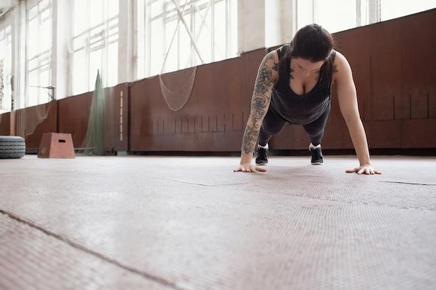 コア強化運動。スポーツホールで板を入れ墨の腕を持つ若い白人女性のローアングルビュー