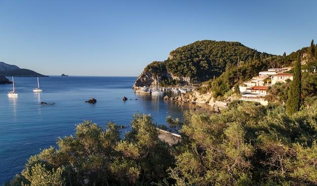 Корфу греция залив палеокастрицаза с яхтами и лодками в кристально чистой лазурной воде