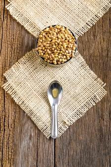 Coriander in bowl on wooden background