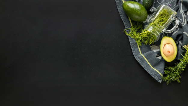 Coriander and halved avocado on tablet cloth against black background
