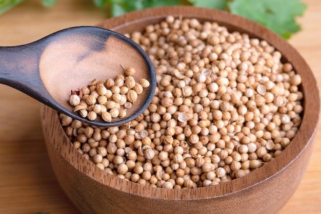 Семена кориандра, свежий кориандр. семена кориандра и листья на деревянных фоне