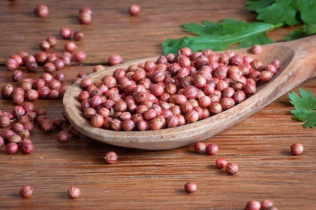 Семена кориандра в деревянной ложке и зеленых листьях на деревянном столе.