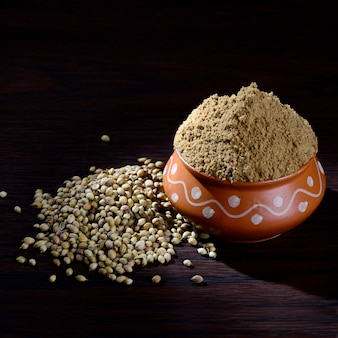 Coriander seeds and powdered coriander in clay pot on wooden background.