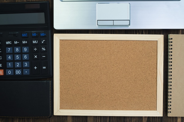 Cork board and calculator and notebook on table