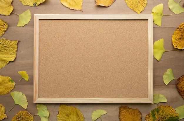 木の葉と木製のテーブルの上のコルクボード。フラットレイ