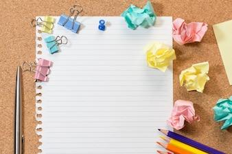 空白の紙、カラフルな空白のノート、カラーの鉛筆、タグ、ごみとプッシュピンとコルクボード