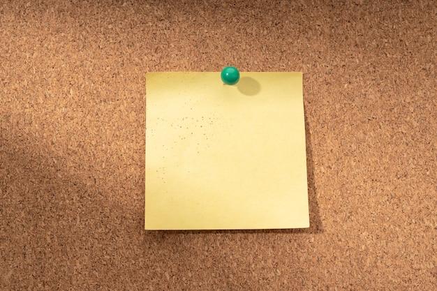 텍스트 및 푸시 핀을 추가하기위한 빈 노란색 메모가있는 코르크 보드