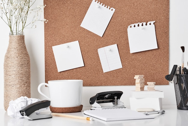 Cork board with office supplies on white background