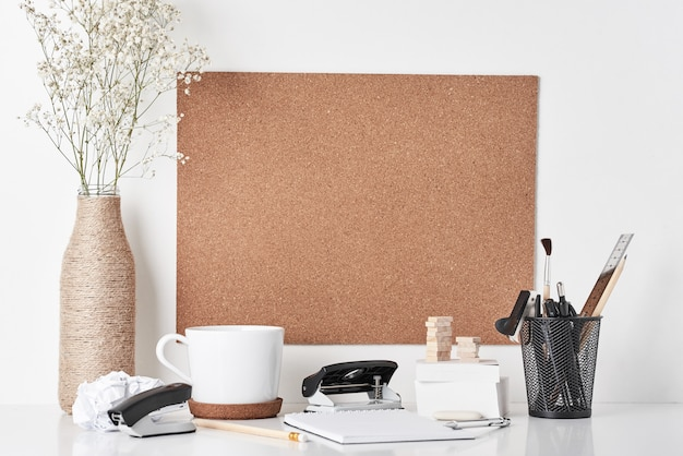 Cork board with office supplies on white