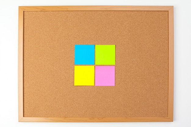 Cork board with several colorful blank notes with pins