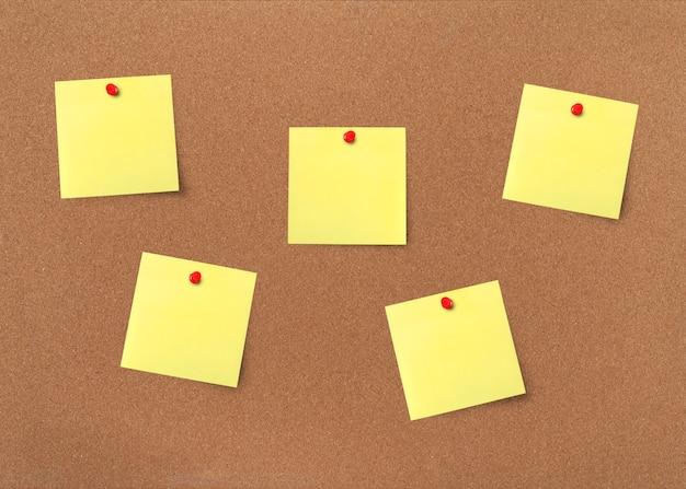 クリッピングパスと黄色の空白のノートとコルクボード