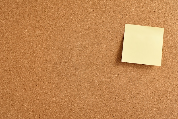 Cork board with a yellow paper blank note