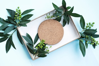 Cork coaster and leaves in the box on blue background
