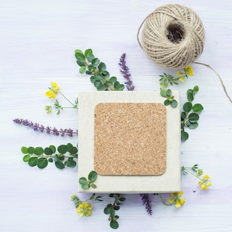 Cork frame with twig and flowers and string spool on wooden textured backdrop