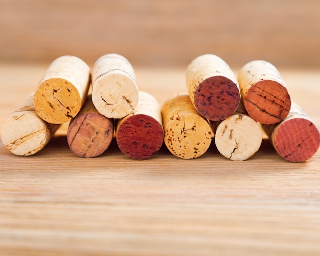 Corks with red stain lie on blur wood background with copy space.